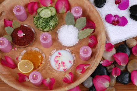 Facial masks, bath salt, body scrubs, petals, orchids, towels, and pebbles in a spa Imagens