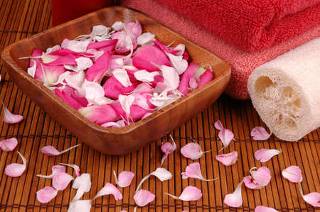 Towels, carnation and rose petals, and bath sponge in a spa Stock Photo - 695581