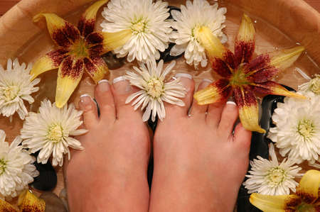 A pair of pedicured feet in a bowl full of water, pebbles, and various fresh flowers Stock Photo - 695499