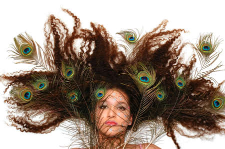 Girl wearing makeup made of rhinestone flowers with peacock feathers in her hair