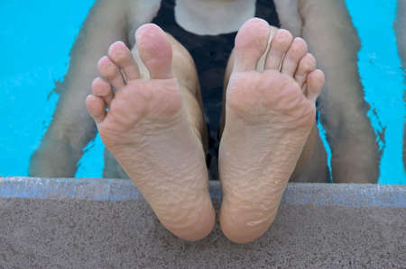Swimmer resting during practice (pruned feet) Stock Photo