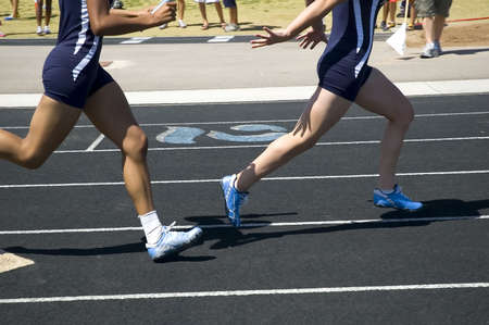 Passing the baton during relay competition Stock fotó