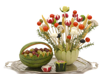 A bouquet of various vegetables in a melon dish and watermelon basket with fruits for a party