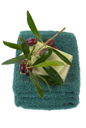 Towel, olive oil soaps and olive branch with olives on it