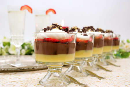 Trifle with chocolate pudding, vanilla pudding, strawberries, chocolate cake pieces, whip cream, walnuts and chocolate curls and champagne