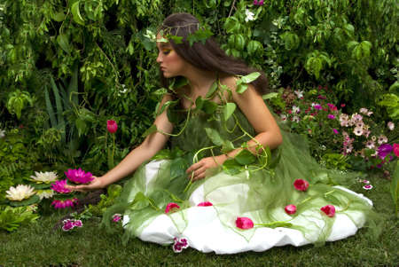 Mother Nature looking upon some of her many beautiful creations in her enchanted garden. This indoor studio shoot is a compilation of many fresh flowers, grass, tree branches and bushes. Stock Photo - 3001566