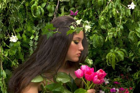 Mother Nature looking upon some of her many beautiful creations in her enchanted garden. This indoor studio shoot is a compilation of many fresh flowers, grass, tree branches and bushes. Stock Photo - 3001568