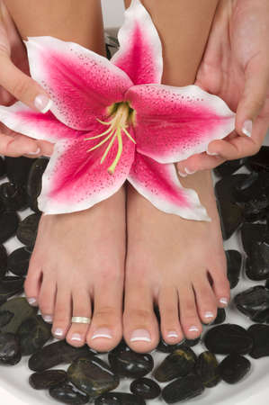 Spa treatment with beautiful lily and therapeutic stones