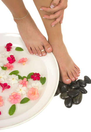 Manicured hand pedicured feet with therapeutic water, pebbles, mint and exotic flowers