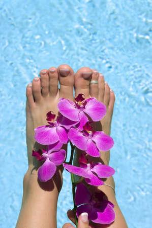 Voeten nabij zwembad met orchideeën Stockfoto