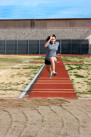 Teen athlete during her triple jump practise 스톡 콘텐츠