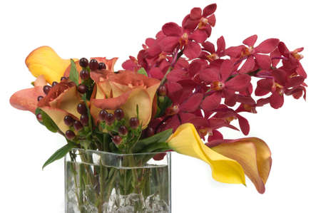 Flower arrangement with lilies, orchids and leaves in a vase