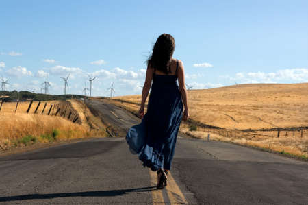 Young woman wearing a silk dress walking down a lonely road toward a field of wind turbines searching of a new beginning for herself and the environment.