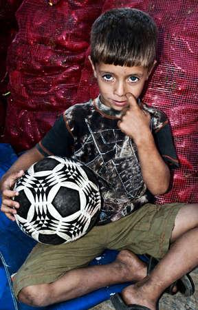 Un niño con su bola de fútbol después de un gran juego infront de sacos de pimiento rojo Foto de archivo - 6073591