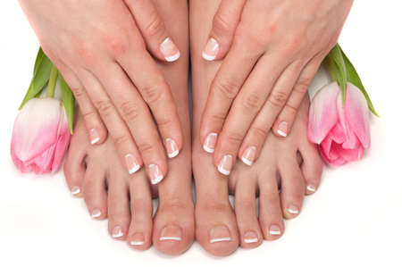 Pedicured feet, manicured hands and aromatic flowers in a spa