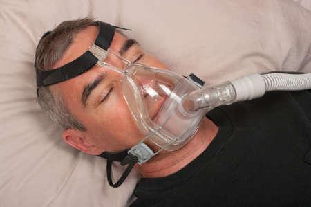 Man sleep with apnea and CPAP machine Stock Photo