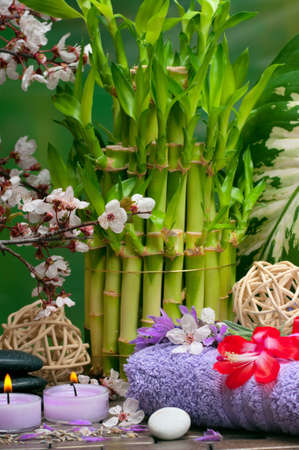 Spa concept with aromatic candles, lavender, healing pebbles, flowers and bamboo