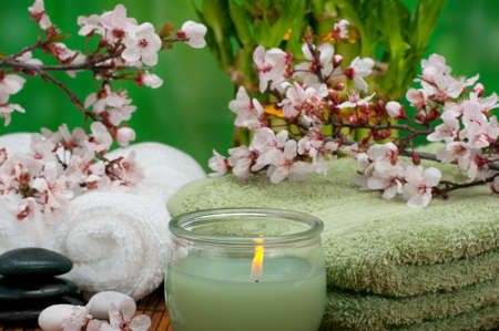 Spa concept with aromatic candle, cotton towels, and healing pebbles