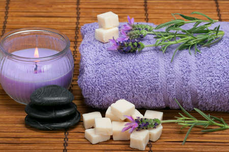 spa scene with lavender, oilve oil soap pieces, healing pebbles, and aromatic candle Imagens