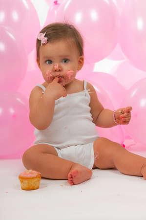 Birthday baby eating her birthday cupcake