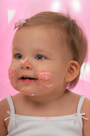 Cute baby girl with cake frosting on her face Banco de Imagens