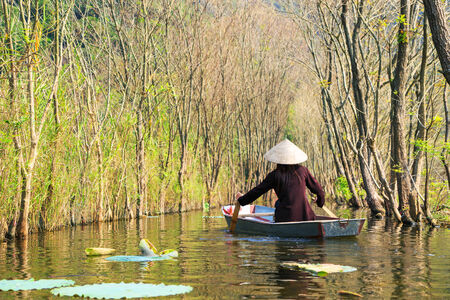 HANOI, VIETNAM - NOVEMBER 2, 2014  girl in traditional costume rowing boat in the flooded forest in MYDUC, VIETNAM  photo