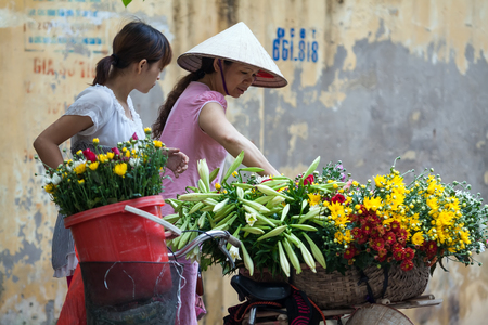 HANOI, VIETNAM - MARCH 31, 2014  Unidentified flower vendor at the flower small market in Hanoi, Vietnam  This is a small market for retail florists and street vendors   Editorial
