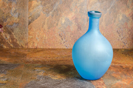 detail of a blue glass bottle against a stone wall
