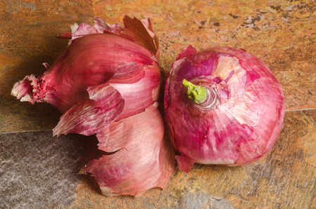two red onions over a stone textured table