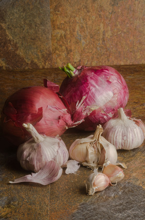 detail of red onions and garlic over a stone textured table