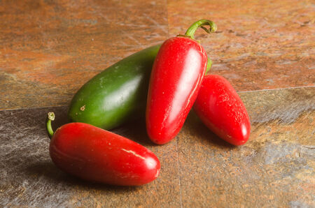 red and green jalapeno peppers on a stone textured table Banco de Imagens