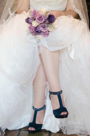 legs of a bride with bouquet and blue shoes Banco de Imagens