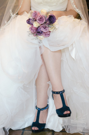 legs of a bride with bouquet and blue shoes photo