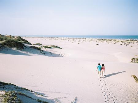 a couple walking on the sand Banco de Imagens