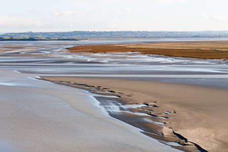 greatly: Sea coast at low tide. The tides can vary greatly, at roughly 14m between high and low water marks. One of Frances most recognizable landmarks. View from the top of the mount Saint Michaels, France Stock Photo