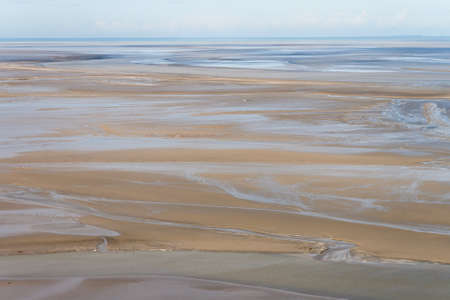 Sea coast at low tide. The tides can vary greatly, at roughly 14m between high and low water marks. One of Frances most recognizable landmarks. View from the top of the mount Saint Michaels, France Stock Photo