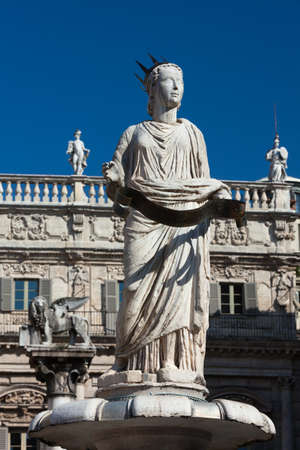 Ancient Sculpture Madonna Verona on Piazza delle Erbe - the towns forum during the time of the Roman Empire. Palazzo Maffei and Venetian lion in the background