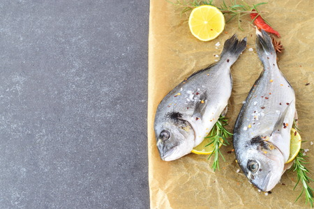 gilthead: Fresh raw dorado fish on a piece of paper with lemon, rosemary, lemon, cherry tomato on a greay background. Healthy eating concept. Mediterranean life style