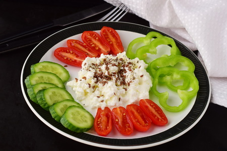 Easy breakfast with paprika, tomato, cucumber with cottage cheese and flax seeds on a plate on a dark background Healthy eating concept. Healthy food