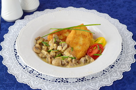 meatless: Potato patties with creamy mushroom sauce in a white plate on a blue cloth. Healthy food concept