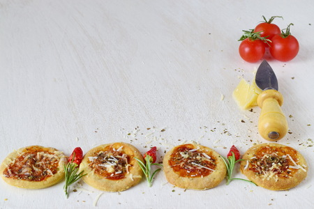 parmezan: White rustic background with homemade biscuit in a form of pizza with chili,rosemary, cherry tomatoes, parmezan, cheese knife and spices. Space for text