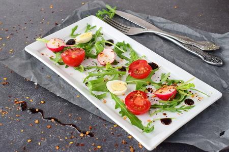 Fresh radish, cherry tomato, quail egg, ruccola with balsamic glaze on a white plate. Mediterranean lifestyle. Healthy food. Stock Photo