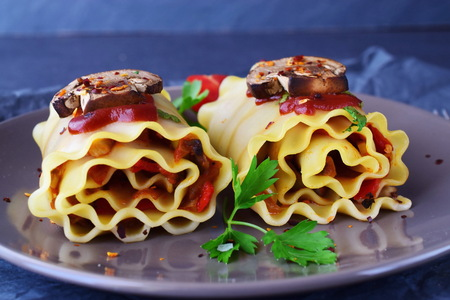 Pasta rolls with vegetables: paprika, onion, olives, mushrooms, tomato on a light brown plate on a grey abstract background. Vegetarian food. Dieting. Mediterranean lifestyle Stock Photo