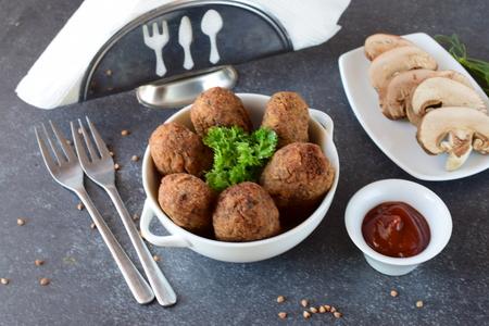 Ballen met boekweit en paddestoelen in een witte kom op een grijze abstracte achtergrond. Dieet. Vasten eten. gezond eten concept
