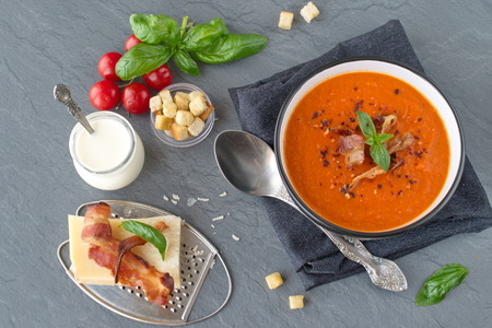 fThick tomato soup with basil and fried becon in a black ceramic bowl on a grey abstract background. Healthy eating conceptresh tomato soup with creme fraiche