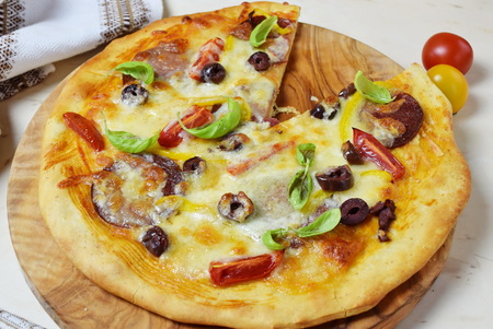 Home made pizza with smoked sausage, olives, tomates, cheese and basil on a olive wood cutting board Banco de Imagens