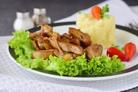 Los testículos fritos del toro con crema y las hierbas sirvieron con el puré de patata en una placa blanca en un fondo abstracto. Concepto de comida saludable