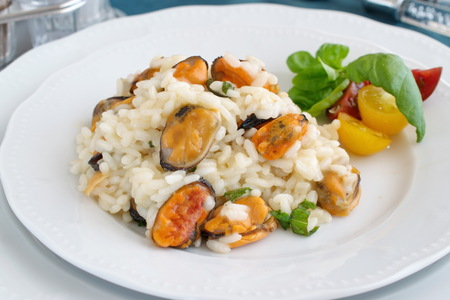 Risotto with mussels on a white plate with basil, cherry tomatoes on a green cloth. Healthy eating concept, Meditarranian life style.