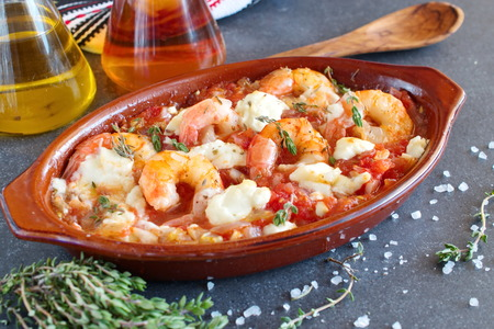 Greek traditional food. Oven backed prawns with feta, tomato, paprika, thyme in a traditional ceramic form. Healthy eating concept. Mediterranian lifestyle. Stock Photo