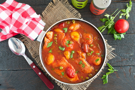 olive green: Fish fillet cooked in tomato sauce with green peas and cherry tomatoes on a plate on a wooden background. Healthy eating concept. Easy cooking
